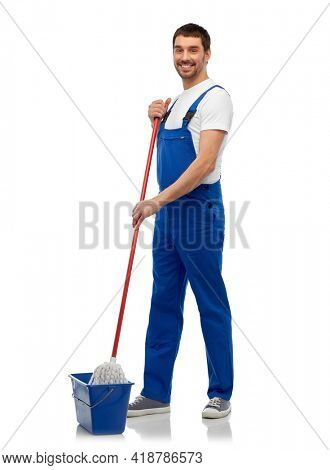 profession, service and people concept - happy smiling male worker or cleaner in overall cleaning floor with wet mop and bucket over white background