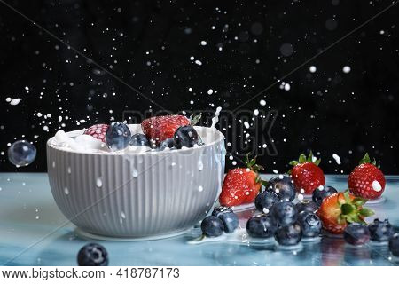 Milk Splash Close Up Of Falling Berries In A Grey Plate Of Milk. Blueberries And Strawberries With M