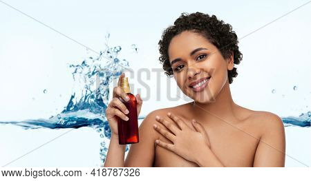 beauty, sun protection and bodycare concept - portrait of happy smiling young african american woman sunscreen oil spray in bottle over white background with bubbles in blue water splash