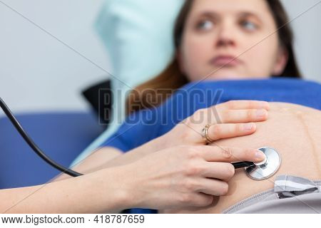 Close-up View Of A Lady Doctor Auscultating A Pregnant Womans Abdomen With A Stethoscope. Profession