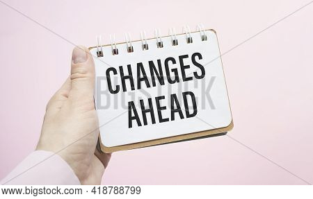 Businesswoman Writes In A Notebook With A Hand Hold Card With Text: Changes Ahead. Pink Background.