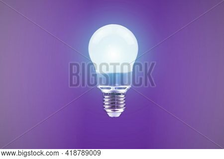 Glowing Energy Saving Light Bulb On Purple Background. Save Electricity.save Money With Energy-savin