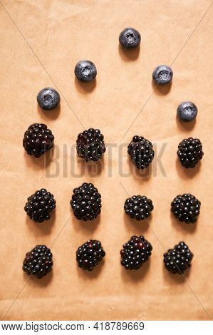 Five Blueberries And Twelve Blackberries On A Beige Background, Laid Out In The Form Of A House. Hig
