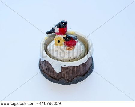 A Snowmans Figure On A Snow-covered Stump. Toy On A White Background.