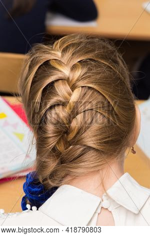 Girls Hairstyle Braided In A Braid Fixed With A Blue Elastic Band Close-up. Hair Styling Is Done Wit