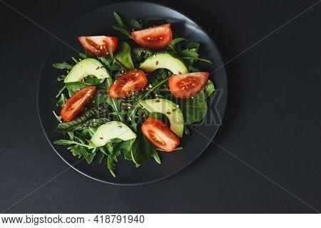 Healthy Salad Of Fresh Vegetables - Tomatoes, Avocado, Arugula, Seeds On Dark Plate