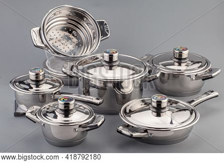 Stainless steel cookware, pots and pans on gray background. Kitchenware set utensils