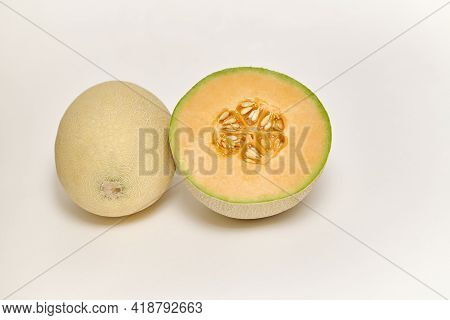 Whole And Sliced Japanese Melon, Honey Melon Or Cantaloupe (cucumis Melo) On A White Background
