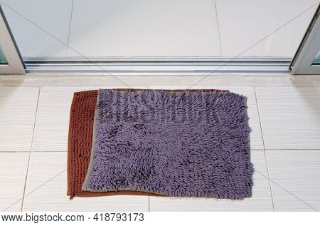 Double Doormat Near The Glass Door To Enter The House, New And Old Doormat Overlay For An Extra Soft