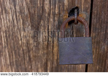 Old Vintage Rusty Metal Door Lock In A Spider Web Hangs On A Closed On A Wooden Door, Copy Space For