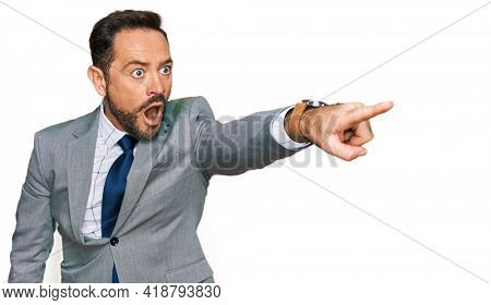 Middle age man wearing business clothes pointing with finger surprised ahead, open mouth amazed expression, something on the front