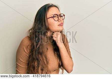 Young hispanic girl wearing casual clothes and glasses touching painful neck, sore throat for flu, clod and infection