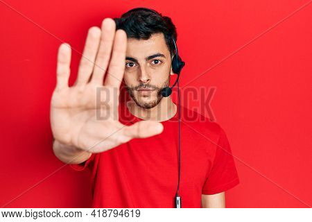 Young hispanic man wearing call center agent headset with open hand doing stop sign with serious and confident expression, defense gesture