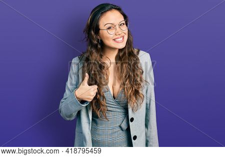 Young hispanic girl wearing business clothes and glasses doing happy thumbs up gesture with hand. approving expression looking at the camera showing success.