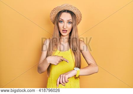 Young blonde girl wearing summer hat in hurry pointing to watch time, impatience, upset and angry for deadline delay