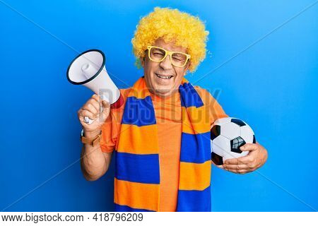 Senior hispanic man football hooligan cheering game holding ball and megaphone winking looking at the camera with sexy expression, cheerful and happy face.