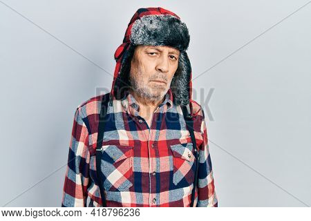 Handsome mature man wearing winter hat with ear flaps with serious expression on face. simple and natural looking at the camera.