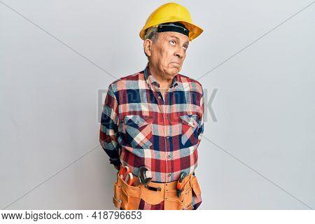 Senior hispanic man wearing handyman uniform smiling looking to the side and staring away thinking.