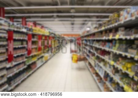 View Abstract Blurred Supermarket Aisle With Colorful Shelves.