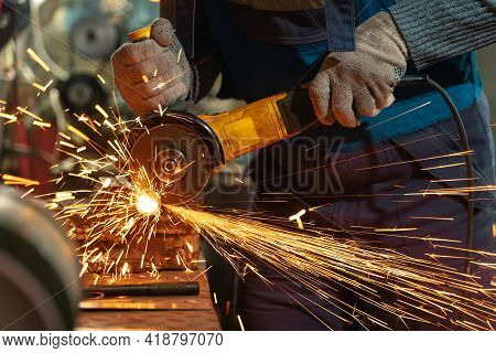 Locksmith In Special Clothes And Goggles Works In Production. Metal Processing With Angle Grinder. S