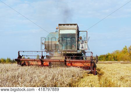 Combine Harvester Harvests Ripe Wheat. Concept Of A Rich Harvest. Agriculture Image.