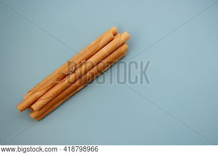 A Bunch Of Wafer Rolls On A Blue Background. Long Wafer Rolls
