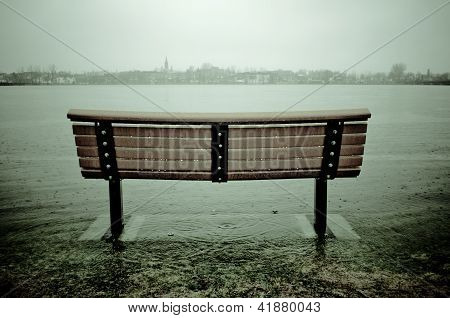 Wooden bench with feet in the river during flood