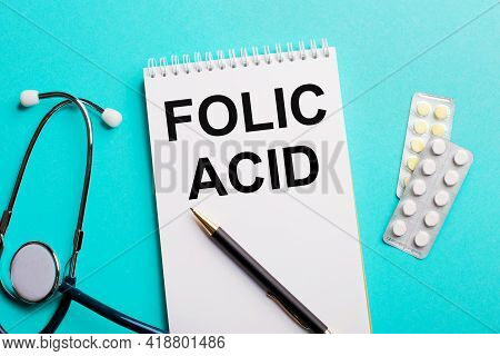 Folic Acid Written In A White Notepad Near A Stethoscope, Pens And Pills On A Light Blue Background.