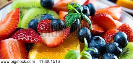 Fresh Summer Salad Of Various Fruits And Berries. Kiwi, Orange, Strawberry And Blueberry On A Plate