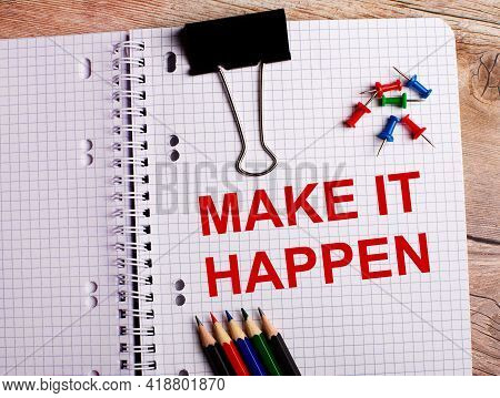 The Words Make It Happen Is Written In A Notebook Near Multi-colored Pencils And Buttons On A Wooden