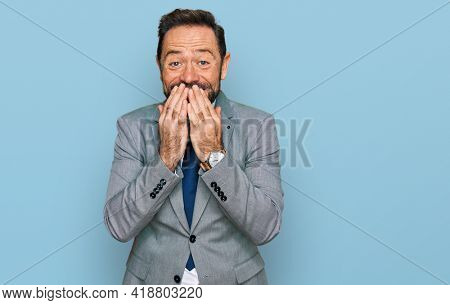Middle age man wearing business clothes laughing and embarrassed giggle covering mouth with hands, gossip and scandal concept