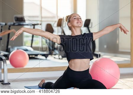 Woman In An Athletic Look With Aerobic Exercise Stretching Loose, Young Sporty Woman Stretching Sit