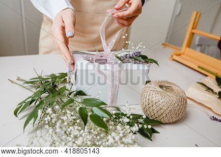 A Florist Decorates A Gift Box With Flowers And A Ribbon On A White Desktop. Only The Hands Are In T