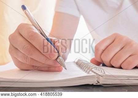 Close-up Of Female Hands With Pen And Notepad. The Woman Makes Notes In Notebook. Concept Of Educati