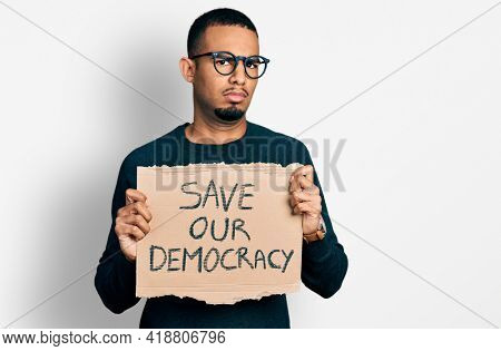 Young african american man holding save our democracy protest banner in shock face, looking skeptical and sarcastic, surprised with open mouth