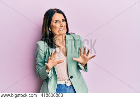 Middle age brunette woman wearing casual clothes disgusted expression, displeased and fearful doing disgust face because aversion reaction.