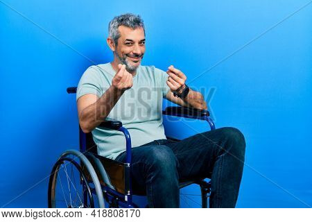 Handsome middle age man with grey hair sitting on wheelchair doing money gesture with hands, asking for salary payment, millionaire business