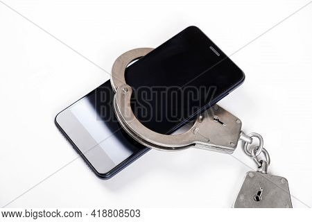 Phone In The Handcuffs On The White Background Closeup