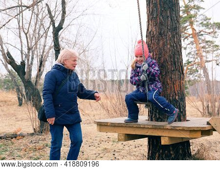 Grandmother And Granddaughter Having  Fun Outdoors Swinging On Wooden Homemade Swing Tied To A Tree
