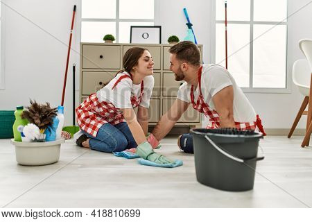 Young caucasian couple washing floor using rag at home.