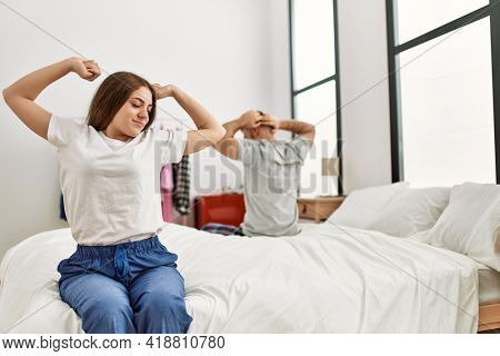 Young caucasian couple yawning and stretching arms sitting on the bed.