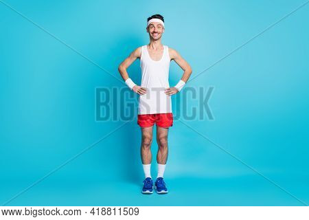 Full Length Photo Of Sporty Man Hold Hand Waist Wear White Singlet Gumshoes Isolated Over Blue Color