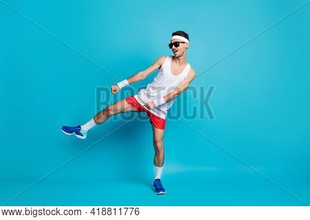 Full Size Photo Of Handsome Sporty Man Dance Funky Wear Sunglass Sportswear Isolated On Blue Color B