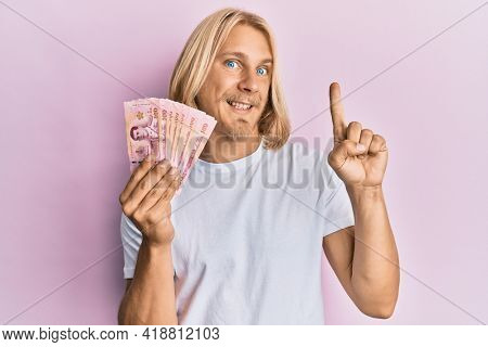 Caucasian young man with long hair holding 100 thai baht banknotes smiling with an idea or question pointing finger with happy face, number one