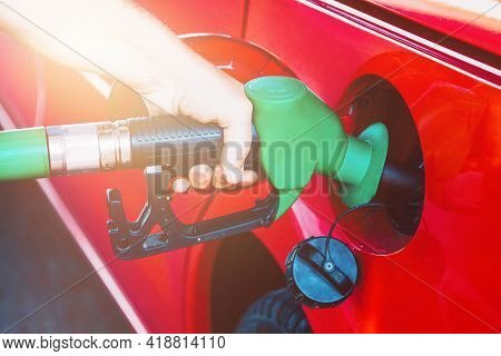 Person Refueling A Red Car At Gas Station
