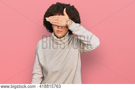 Young hispanic girl wearing wool winter sweater covering eyes with hand, looking serious and sad. sightless, hiding and rejection concept