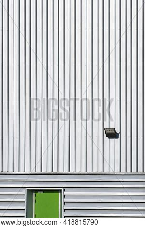 Front View Of Green Steel Door With Led Spotlight Solar Cell On Corrugated Metal Wall Of Large Indus
