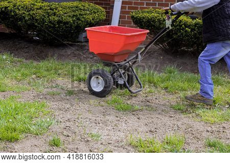 The Gardener Works With Seeding And Fertilizing The Lawn Sows Fresh Grass On Residential Backyard