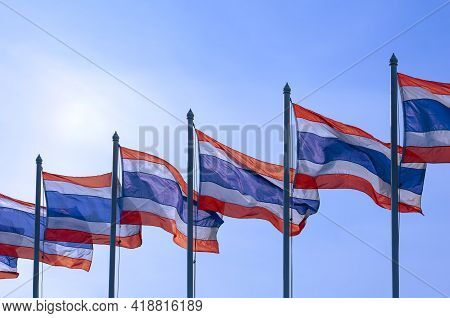 Row Of Many Thai Flags On Flagpoles Waving In The Wind Against Blue Clear Sky In Sunny Day