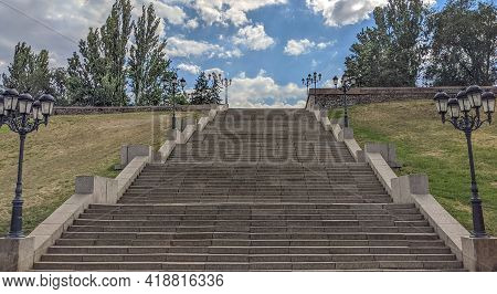 Bottom View Of A Wide Stone Pedestrian Staircase In The City. Thick White-gray Clouds Are At The Top